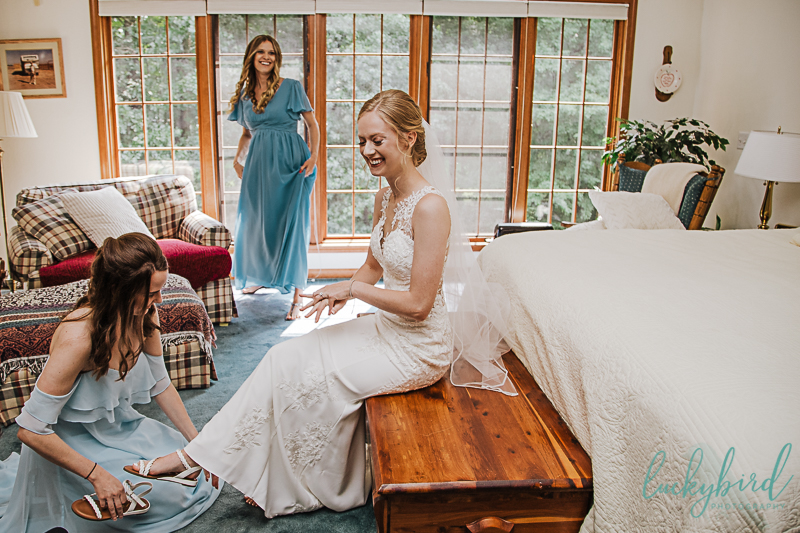bridesmaids helping bride get her shoes on during toledo wedding