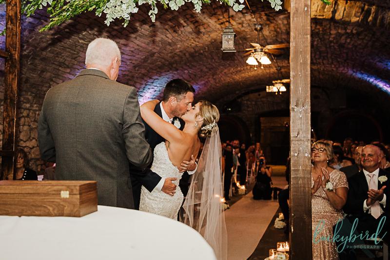 first kiss at gideon owen wine cellar wedding ceremony