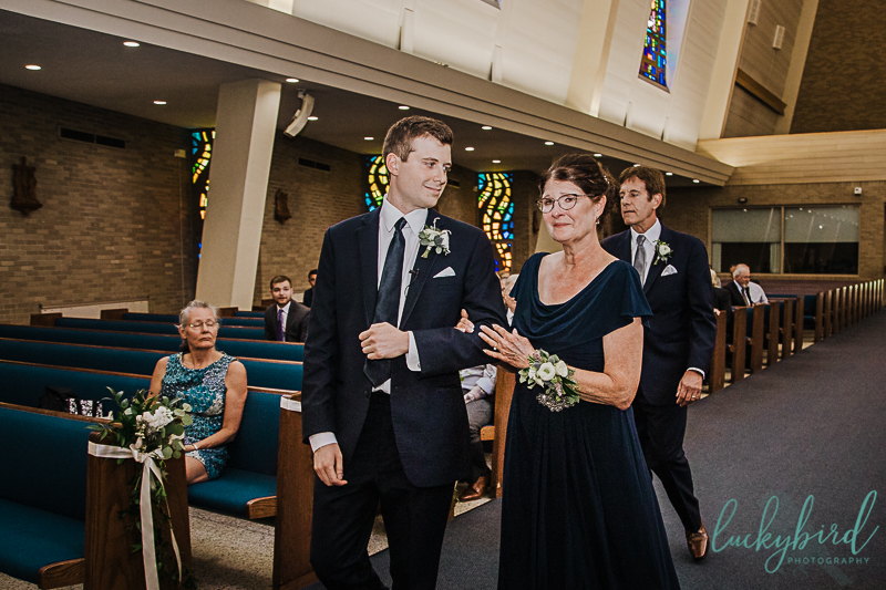 groom and mom walking down the aisle