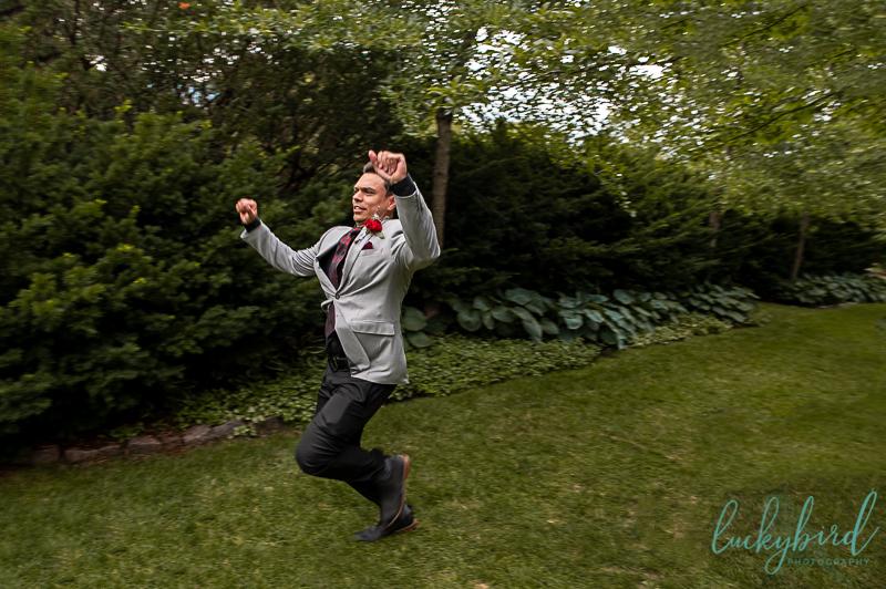 groom running down the aisle at toledo zoo wedding