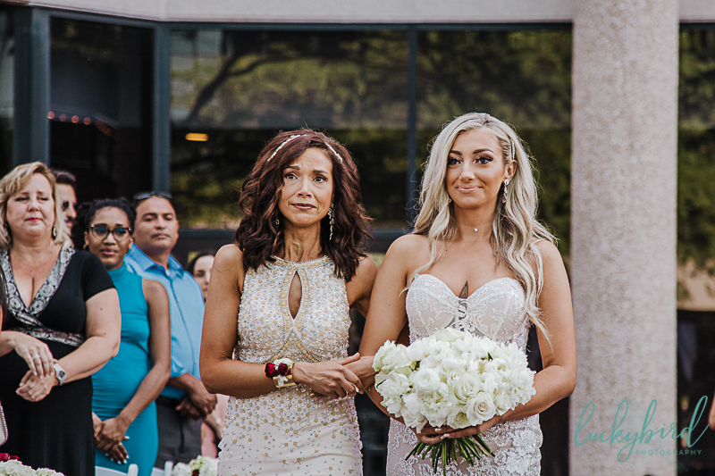 bride and mom walking down the aisle at renaissance toledo outdoor ceremony