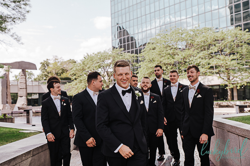 groom laughing during renaissance toledo groomsmen wedding photos