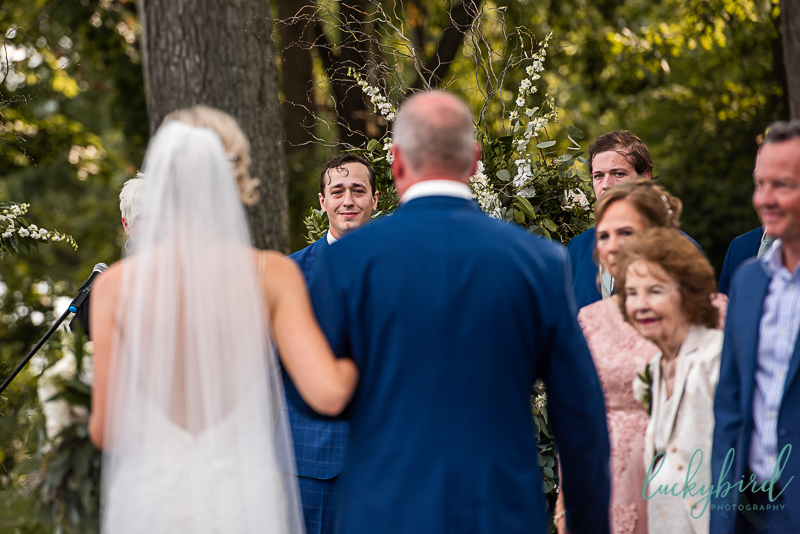 groom-seeing-bride-walk-down-the-aisle-at-toledo-country-club