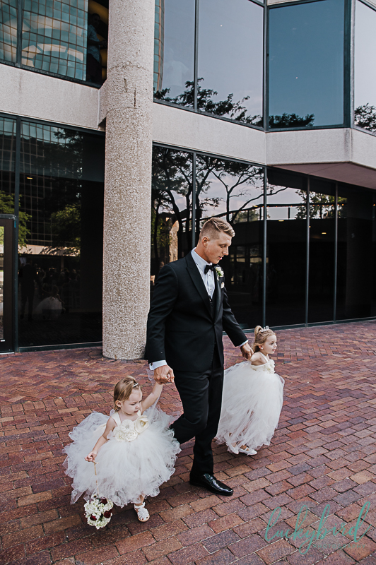 groom walking down the aisle with daughters
